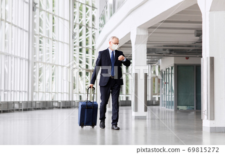 old businessman in mask with travel bag at airport 69815272