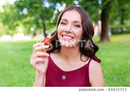 happy woman eating strawberry at summer park 69815353