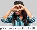 happy asian woman showing hand heart gesture 69815400
