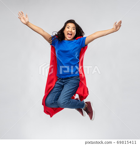 happy asian woman in red superhero cape jumping 69815411