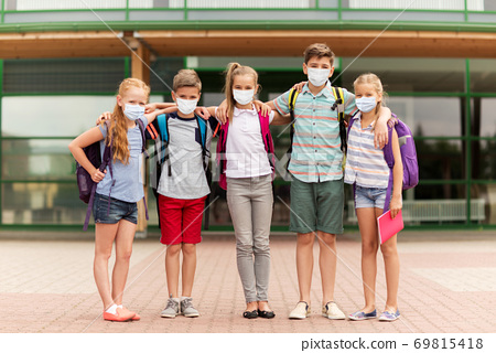 group of students in masks hugging over school 69815418