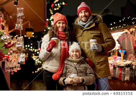 family with takeaway drinks at christmas market 69815558