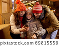 happy family with smartphone at christmas market 69815559