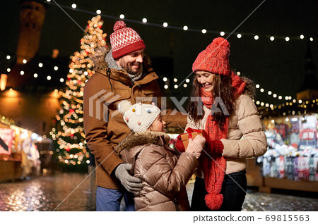 happy family with gift at christmas market in city 69815563