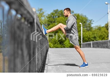 man stretching leg on bridge 69815619