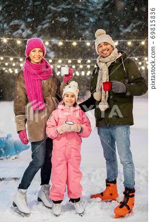 happy family drinking hot tea on skating rink 69815836