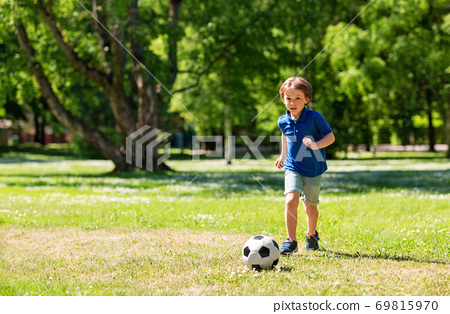 happy little boy with ball playing soccer at park 69815970