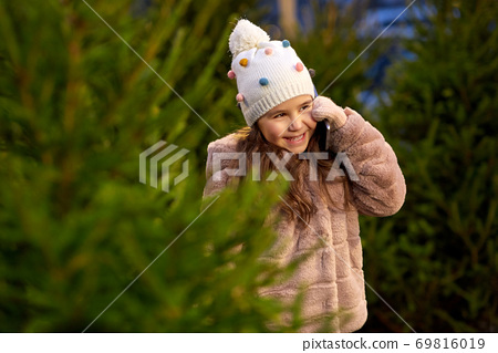 girl calling on smartphone over christmas trees 69816019