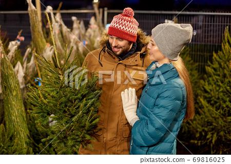 happy couple buying christmas tree at market 69816025