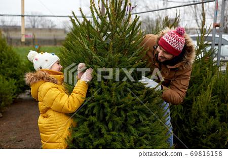happy family choosing christmas tree at market 69816158