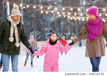 happy family at outdoor skating rink in winter 69816176