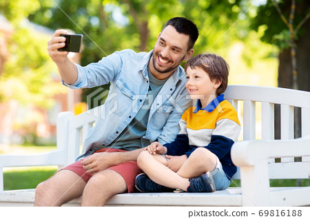 father and son taking selfie with phone at park 69816188