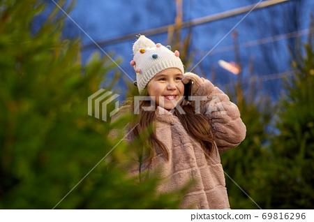 girl calling on smartphone over christmas trees 69816296