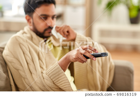 sick man with paper tissue and tv remote at home 69816319