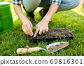 woman planting flower seeds to pots tray with soil 69816361