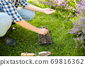 woman planting flower seeds to pots tray with soil 69816362
