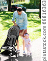 father with child and stroller walking at park 69816363