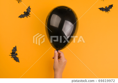 Bats and a black balloon on an orange background. Halloween decor 69819972