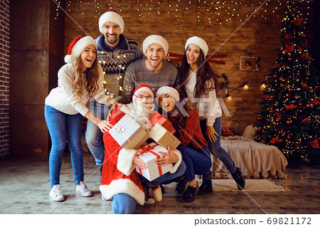 Friends in Santa's hats change gifts at the Christmas party 69821172