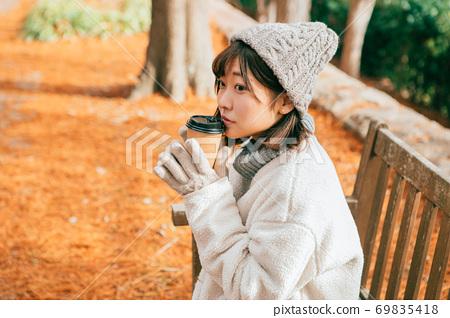 一個女人坐在公園的長椅上,喝一杯熱飲料 69835418