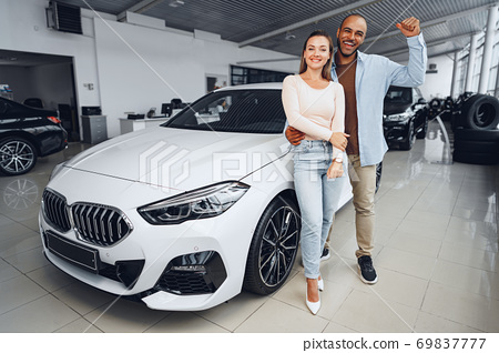 Happy couple of caucasian woman and african american man standing near their new car inside car salon 69837777
