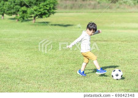 A boy kicking a soccer ball 69842348