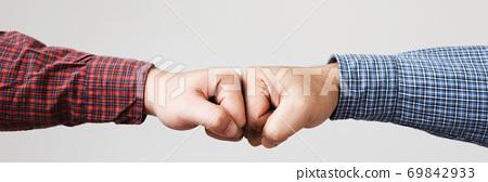Closeup of arm wrestling or friendly handshake gesture. 69842933