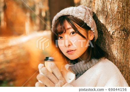 겨울 야외에서 뜨거운 커피를 마시는 여성 69844156