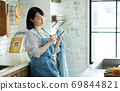 Housewife looking at a smartphone in the kitchen 69844821