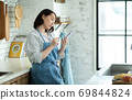 Housewife looking at a smartphone in the kitchen 69844824