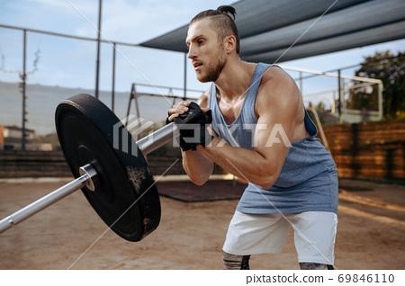 Man prepares barbell weights, street workout 69846110