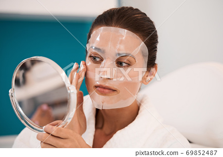 Woman looking at her face in mirror 69852487