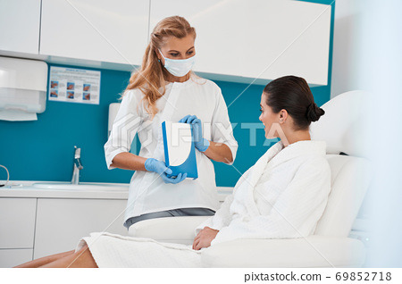 Doctor showing injection box to her patient 69852718