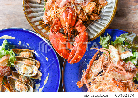 Grilled Lobster sausage ham vegetables and cheese spaghetti seafood buffet , Grilled shrimps prawns , mussel baked with cheese Shellfish seafood plate with lobster dinner food cooked top view 69862374