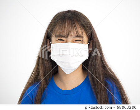 teenager  Asian  girl smiling and wearing  medical mask 69863280