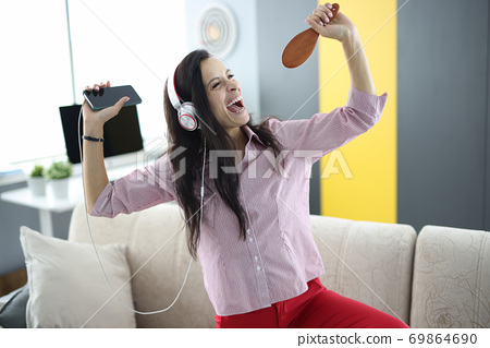 Woman in headphones on couch holds smartphone in her hands and pretends to sing 69864690
