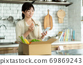 Housewife with an apron standing in the kitchen 69869243