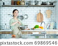 Cute woman standing in the kitchen 69869546