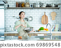 Cute woman standing in the kitchen 69869548