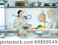 Cute woman standing in the kitchen 69869549