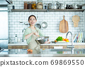 Cute woman standing in the kitchen 69869550