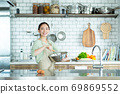 Cute woman standing in the kitchen 69869552