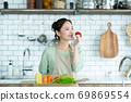 Cute woman standing in the kitchen 69869554