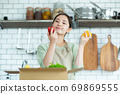 Cute woman standing in the kitchen 69869555