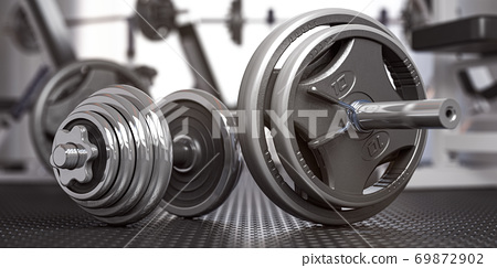Dumbbell and barbell on the floor of gym. Close up fItness equipment. Sport, fitness and bodybuilding concept background 69872902