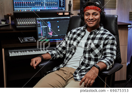 Portrait of happy young man, male artist smiling at camera while sitting in recording studio 69875353