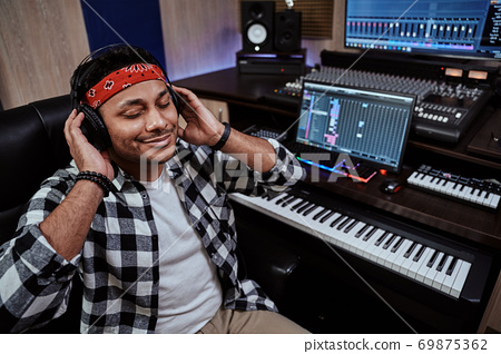 Young man, male artist in headphones sitting with eyes closed while listening to music in recording studio 69875362