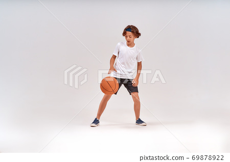 Competition. Full-length shot of a teenage boy playing basketball while standing isolated over grey background 69878922