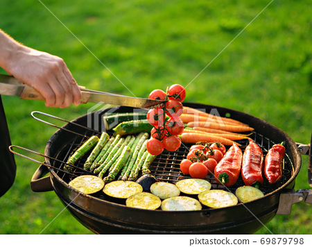 Scene of a man grilling vegetables outdoor. 69879798