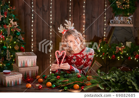 Woman dressed in christmas design sweater, deer horn hoop, posing with candy. Handmade christmas wreath on table for holiday, christmas decoration and composition 69882685